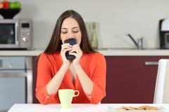 Zweifelhafte Frau, die sich wundert, wenn sie am Telefon nennen muss Lizenzfreie Stockfotos