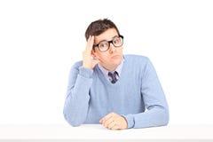 Zweifelhafter Kerl, der auf einer Tabelle sitzt und denkt Lizenzfreie Stockfotografie