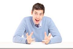 Zweifelhafter Mann, der mit den Händen sitzt und gestikuliert Stockfotos
