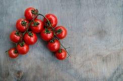 Zweig von frischen roter-Deliciouskirschtomaten auf einem alten hölzernen Vorsprung Stockbilder