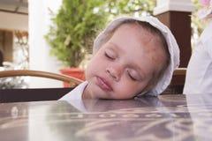 Zweijähriges Mädchen schlafend an einem Tisch im Straßencafé Stockbild