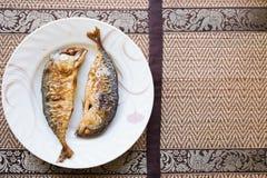 Zweimal von gebratenen Fischen auf weißem Teller mit thailändischer Kunstart auf backgro Stockfotografie