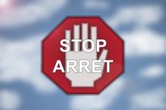 Zweisprachiges Stoppschild auf unscharfem Wolkenhintergrund Stockbilder