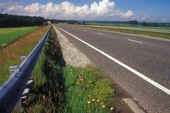 Zweispurige Straße durch Ackerland Lizenzfreies Stockfoto