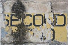 Zweite Hand auf einer Backsteinmauer stockfotografie