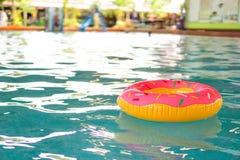 Zwem ring die op blauw water met een luchtige golfbezinning drijven stock foto