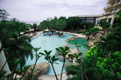 Zwembad bij het overzees, zonlanterfanters naast de tuin en gebouwen Royalty-vrije Stock Foto