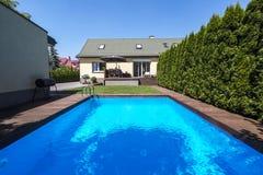 Zwembad in de tuin van huis met bomen tijdens de zomer r royalty-vrije stock foto