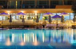 Zwembad, deckchairs en paraplu's Royalty-vrije Stock Afbeeldingen