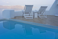 Zwembad en ligstoelen met overzeese mening Royalty-vrije Stock Foto