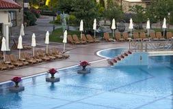 Zwembad met deckchairs Stock Afbeelding