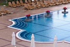 Zwembad met deckchairs Stock Foto