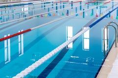 Zwembad met duidelijke rode en witte stegen Leeg zwembad zonder mensen met stil bevindend water stock foto