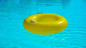 Zwembad met een helder gele opblaasbare ring stock footage