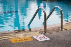 Zwembad met ladder en teken stock afbeeldingen