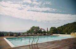 Zwembad met sunbeds en zonparaplu en bergen op de achtergrond stock afbeelding
