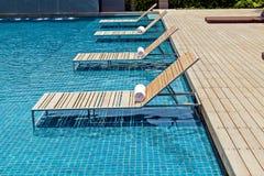 Zwembad met witte deckchairs Royalty-vrije Stock Fotografie