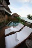 Zwembad overzeese mening, zonlanterfanters naast de tuin en gebouwen Stock Afbeelding