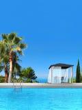 Zwembad, palmen, cipres en paviljoen Stock Foto