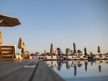 Zwembad van het hotel van de luxevakantie, verbazende mening Ontspan dichtbij pool met leuning, sunbeds, zonlanterfanters en para royalty-vrije stock foto's
