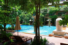 Zwembad, zonlanterfanters naast de tuin en gebouwen Royalty-vrije Stock Afbeeldingen