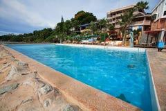 Zwembad, zonlanterfanters naast de tuin en gebouwen Stock Afbeeldingen
