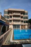 Zwembad, zonlanterfanters naast de tuin en gebouwen Royalty-vrije Stock Foto