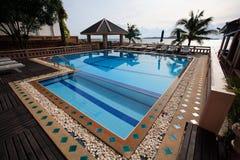 Zwembad, zonlanterfanters naast de tuin en gebouwen Royalty-vrije Stock Afbeelding