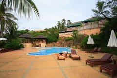 Zwembad, zonlanterfanters naast de tuin en gebouwen Stock Foto's