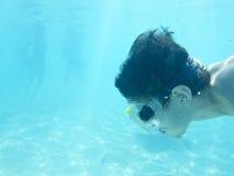 Zwemmen van de jongen onderwater in oceaan Stock Foto's