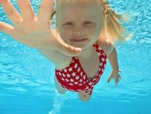 Zwemmen van het kind onderwater in pool Stock Afbeeldingen