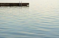Zwemmend dok met ladder bij de rand van mooie blauwe rust watersrs stock foto's