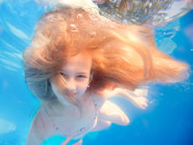 Zwemmend jong meisje met langharige onderwater in pool Stock Foto