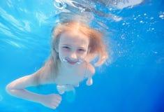 Zwemmend jong meisje onderwater in pool Stock Afbeeldingen