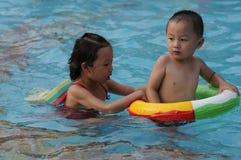 Zwemmend jongen en meisje Stock Foto's