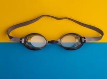 Zwemmende beschermende brillen op blauwe en gele achtergrond Royalty-vrije Stock Afbeelding