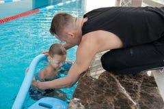 Zwemmende trainer bijwonende jongen royalty-vrije stock fotografie