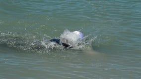 Zwemmer die aan het eind van de route in de triatlonconcurrentie komen die in een meer zwemmen stock video
