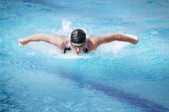 Zwemmer die de vlinderslag, voorzijde uitvoert Stock Afbeelding