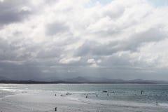 Zwemmers uit in grijze oceaan met golven op een stormachtige dag stock foto