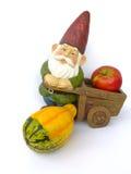 Zwerg mit Schubkarre, Apfel und Kürbis Lizenzfreie Stockfotos