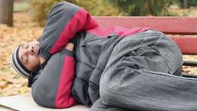 Zwerver in jasje en jeans die op bank slapen, die warm, armoede proberen te houden stock videobeelden