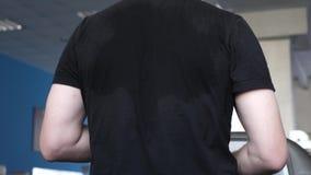 Zwetende achtermensen in T-shirtclose-up r langs versterkend spieren van hart en benen royalty-vrije stock afbeeldingen