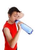 Zwetende jongen die gebotteld water drinkt stock foto's