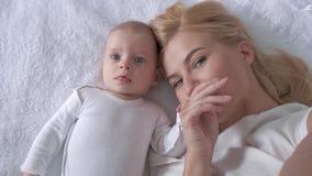 Związku dziecko i matka, potomstwa wychowywamy z słodkim dziecięcym dziewczyny lying on the beach na białym łóżku i pozujemy na k zbiory wideo