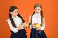 Zwiększenie studencka akceptacja owoc Zakłócać bezpłatną świeżą owoc przy szkołą Dziewczyna dzieciaków mundurka szkolnego pomarań zdjęcia stock