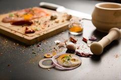 Zwiebel im Vordergrund mit rohem Fleisch und Würzen im Hintergrund Lizenzfreies Stockfoto
