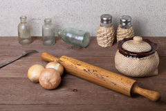 Zwiebel, Salz, Pfeffer, Nudelholz, alte Flaschen und Gabel auf dem ol Lizenzfreie Stockfotografie