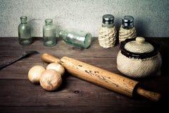 Zwiebel, Salz, Pfeffer, Nudelholz, alte Flaschen und Gabel auf dem ol Lizenzfreie Stockbilder
