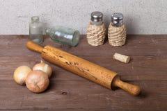 Zwiebel, Salz, Pfeffer, Nudelholz, alte Flaschen und Korken auf dem ol Lizenzfreies Stockbild